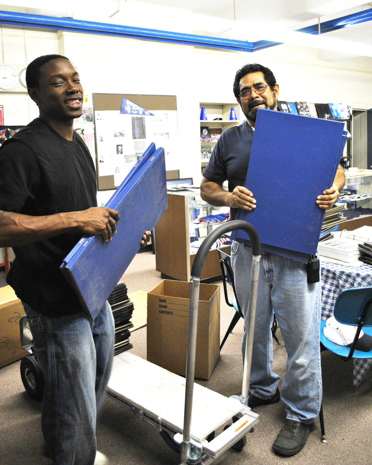 James Hoke and Carlos Gonzales unload bound Mentors they transported from MHS West to the Alumni Center.