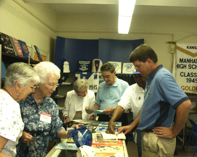 Class of 1944 checks out old programs on visit to Alumni Center.