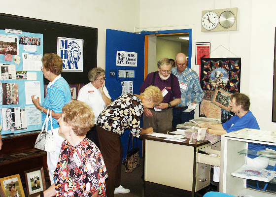 Class of 1954 reunion goers take the time to sign into the Alumni Center.