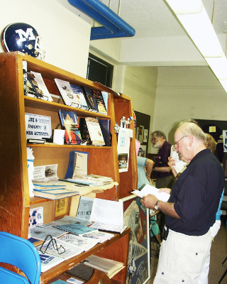 The growing MHSAA Library shelf gets checked out during the Class of 1954 reunion.