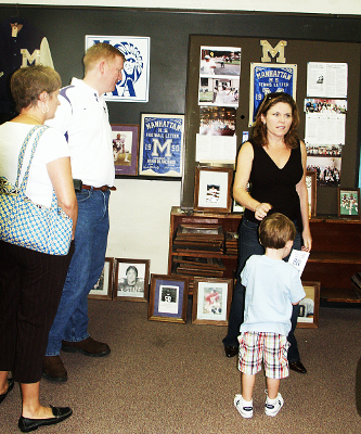 A Class of 1988 Mom converses while her son checks out the neat stuff in the Alumni Center.