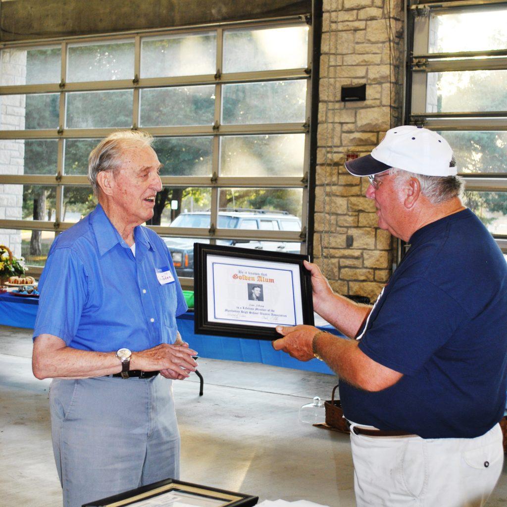 Dave Fiser presents Jim Johns with Golden Alumn certificate.